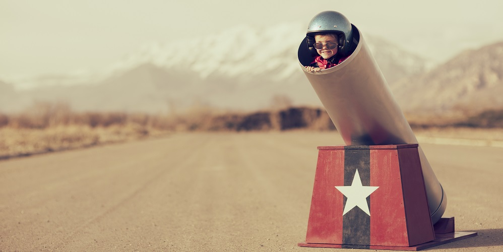 A young boy is ready to go places, real quick, with the help of a human cannon. Boom.